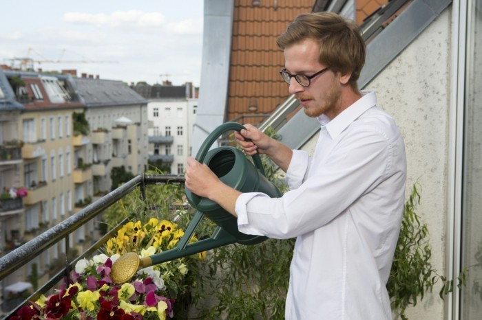red-haired handome young man watering flowers on balcony